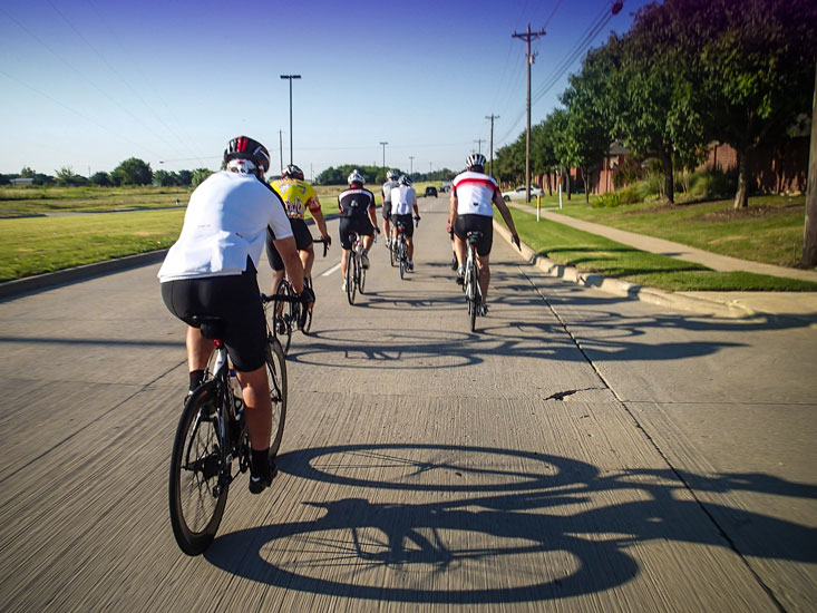 A PBA rider points out the crack in the road on the right, which can swallow a bike tire easily.